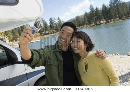Couple Using Cell Phone Camera at Lake
