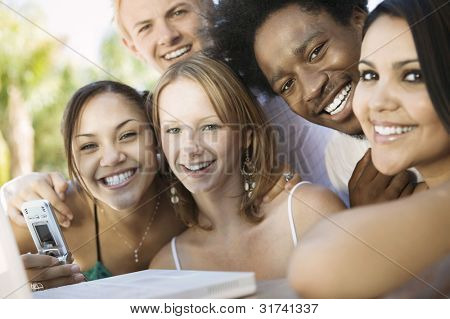 Friends Using Cell Phone and Laptop