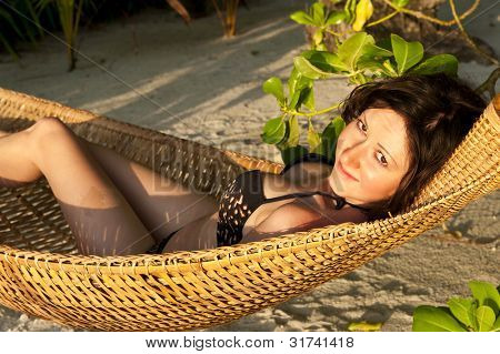 Girl is tanning in the hammock under the palms on the tropical Maldivian beach in the evening sun