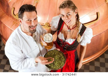 Woman and her male brewer with beer stein and hops in her brewery