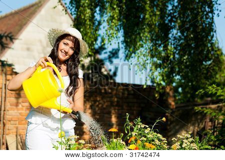 Gardening in summer - woman watering flowers with a yellow watering can, she is wearing a hat