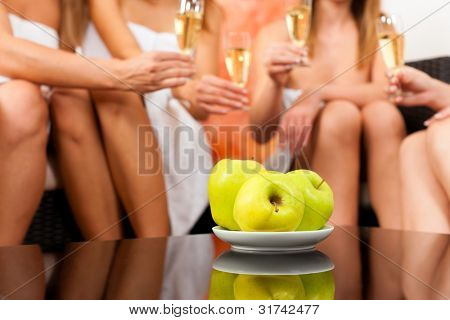 Wellness - young, happy female friends drinking champagne in spa and have fun