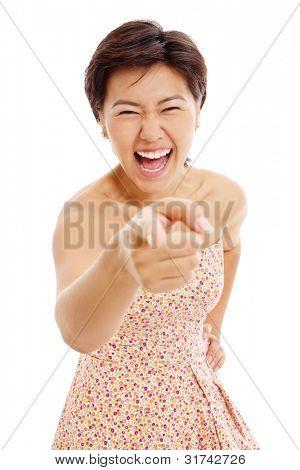 Hermosa chica asiática mostrando el dedo índice en algo y reír mucho. Aislado en blanco backg