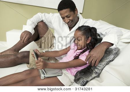 Father and Daughter Watching Movie on Portable DVD Player