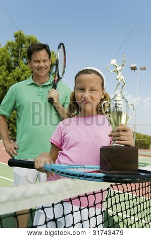 Father and Daughter Holding Tennis Rackets and Trophy