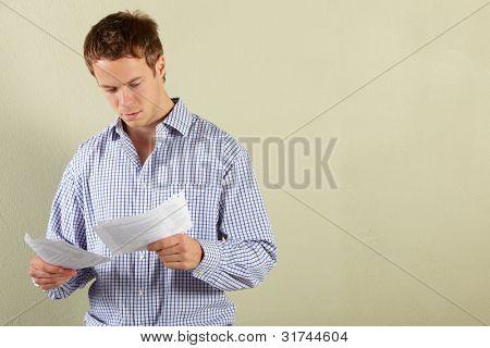 Studio Shot Of Young Man Looking at Bills