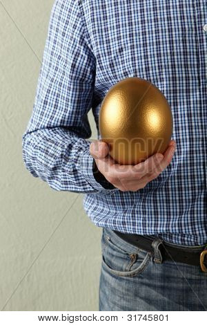 Cropped Studio Shot Of Man Holding Golden Egg