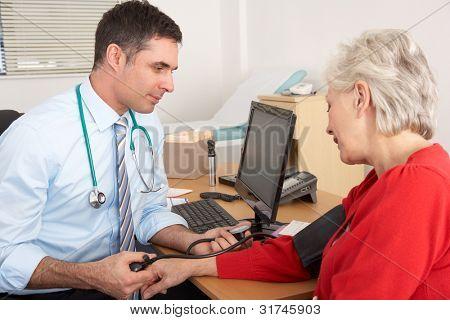 British doctor taking senior woman's blood pressure