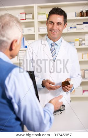 American pharmacist with senior man in pharmacy