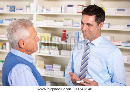 UK pharmacist serving  senior man in pharmacy