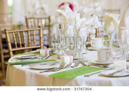 This is a wedding table set for dinner service. There are green menus on the table, but you cannot read the writing.