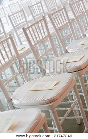 Fancy white chairs set up during a wedding ceremony. There is paper with the schedule on it. You cannot read the words.