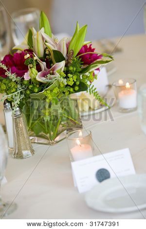 Wedding centerpiece on a table set for fine dining. Shallow depth of field, focus on the bouquet