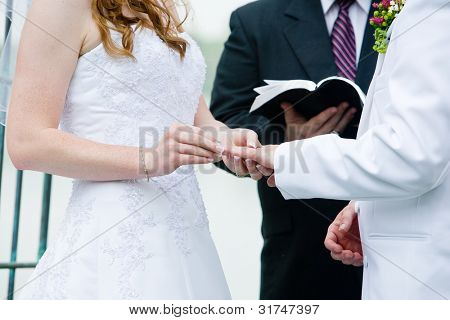 A bride putting the wedding ring on her grooms finger