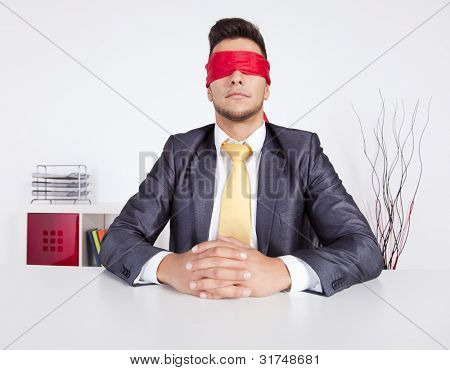Businessman at his office with scarf covering his eyes