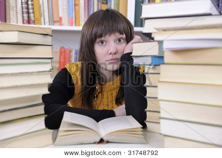 Female student studying with books in a library