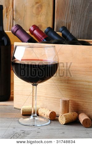 A glass of red wine in front of a wooden case of wine bottles on a rustic wood background. Vertical Format.