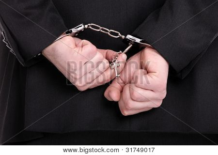 A picture of a businessman trying to unlock his handcuffs
