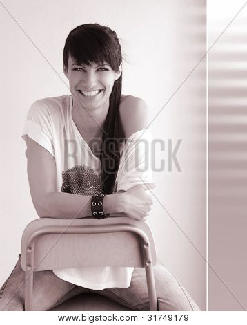 Portrait of a cool trendy happy laughing girl sitting backwards in a stool with pink sepia retro toned treatment