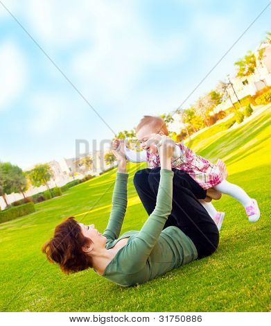 Mother and cute baby daughter playing outside at summer backyard, young woman with little girl, female holding child, beautiful mommy and cute kid lying on the grass, happy family in nature concept