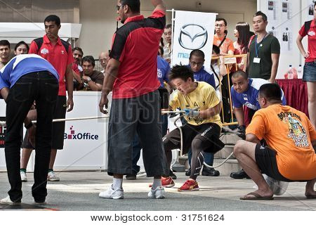 TOA PAYOH, SINGAPORE - MARCH 24 : Contender for Strongwoman Challenge Feng Yi Chew  in the Mazda CX-7 car pull category in the Strongman Challenge 2012 on March 24, in Toa Payoh Hub, Singapore.