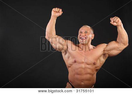 ausgeklappt gebräunte glücklich Bodybuilder löst seine Fäuste oben im schwarzen studio