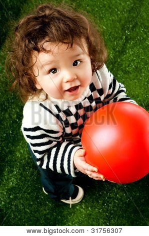 little kid with a red ball on the green grass