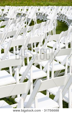 Chairs set up for wedding ceremony outside in the grass