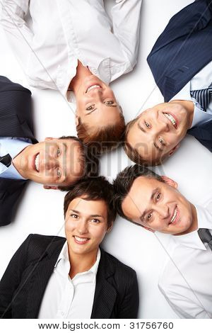 Five business people lying in circle, looking at camera and smiling