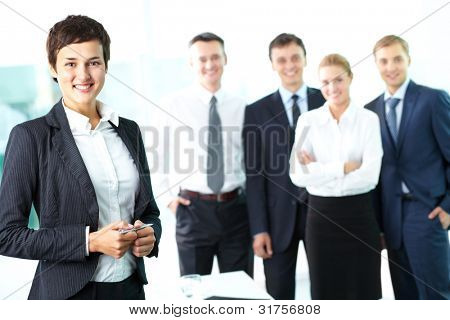 Attractive woman looking at camera and smiling against her business team