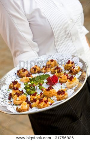 food being served by a waiter during a wedding or catered social event