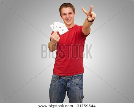 portrait of a young man holding cards while doing a winner gesture against a grey background
