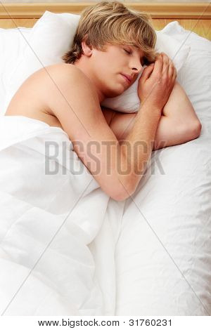 Man comfortably sleeping in his bed.