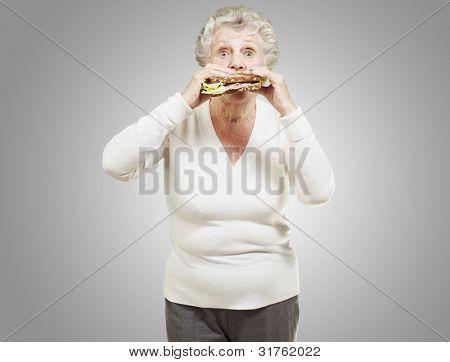 senior woman eating a healthy sandwich against a grey background