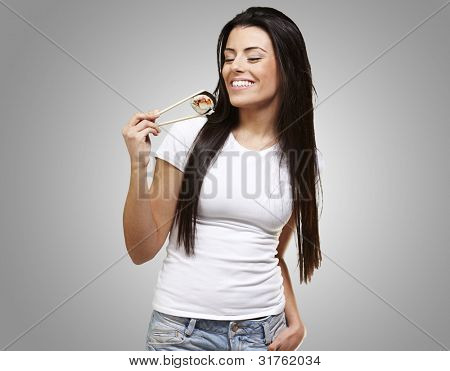 young woman eating a sushi piece against a grey background