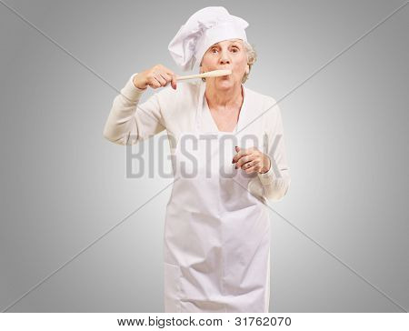 portrait of cook senior woman with a wooden spoon covering her mouth over a grey background