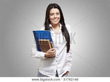 joven estudiante sosteniendo libros y sonriendo sobre un fondo gris