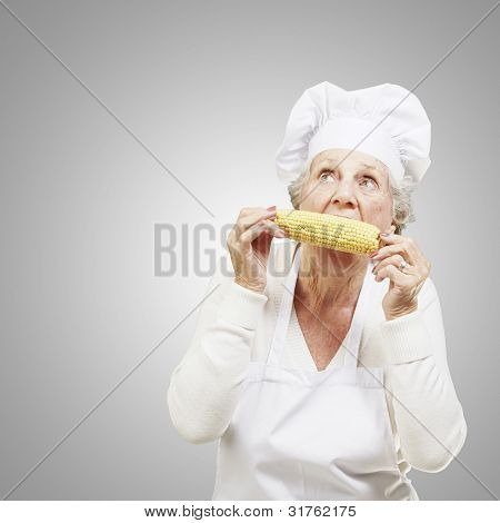 senior woman cook eating a corncob against a grey background