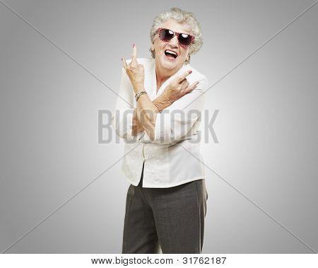 Retrato de una mujer mayor haciendo un símbolo de la roca sobre un fondo gris