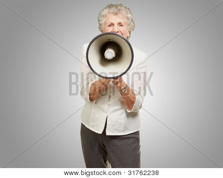 portrait of a senior woman screaming with a megaphone over a grey background