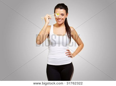 young woman covering her eye with a sushi piece against a grey background