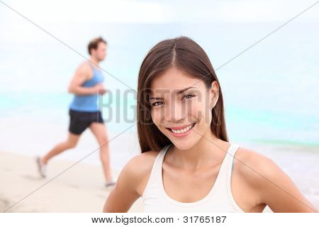Runner workout woman portrait on beach with man running in background. Happy smiling mixed race Asian / Caucasian female fitness sport model during outdoor workout.