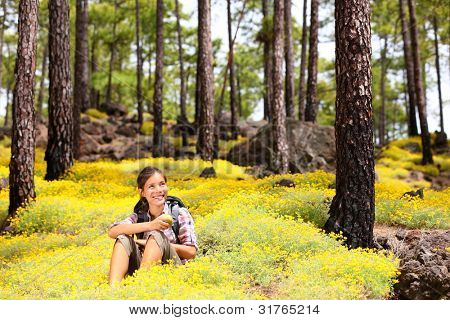Woman hiker sitting relaxing after hiking eating apple in spring flowers in forest floor. Forest landscape, From Tenerife, Canary Islands, Spain