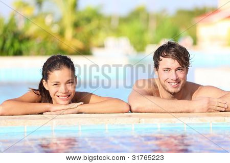Young couple in pool - summer travel photo of two happy smiling people relaxing in tropical resort swimming pool. Caucasian man, Asian woman, focus on male model.