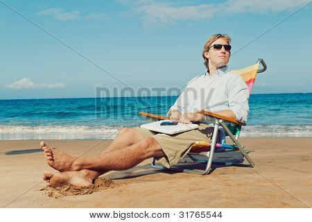 Young Attractive Man Relaxing at the Beach with Laptop Computer