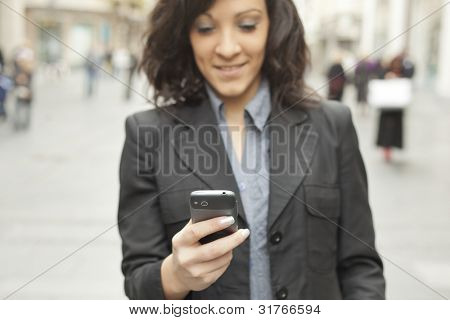Young Woman with smartphone walking on street, downtown. In background is blured street. Phone in focus