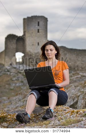 Beautiful girl working on laptop outdoor. Old and new concept.