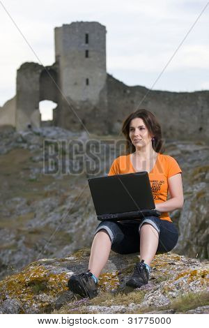 Beautiful girl working on laptop outdoor.Old and new concept.