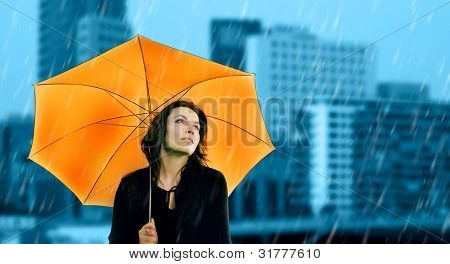 Beautiful young woman with orange umbrella on rainy day