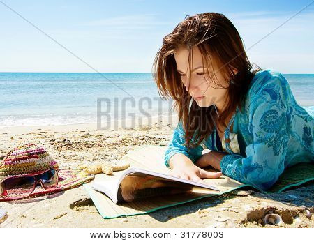 Pretty girl reading novel at beautiful beach